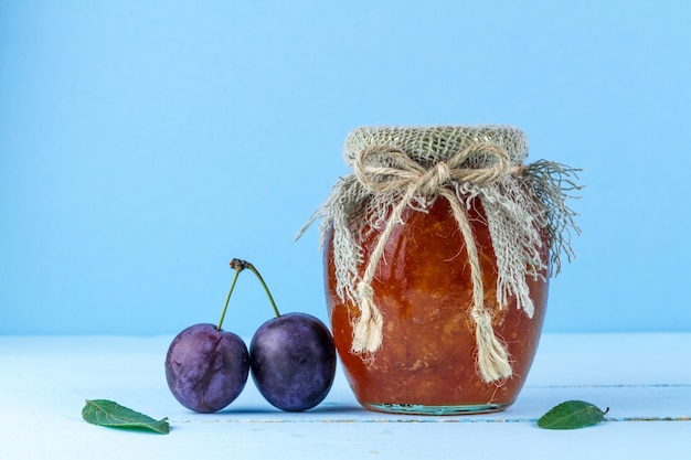 A jar of plum homemade jam and two plums,