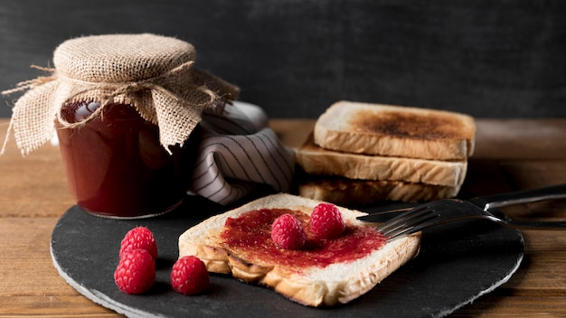 Jar of raspberry jam with bread and knife