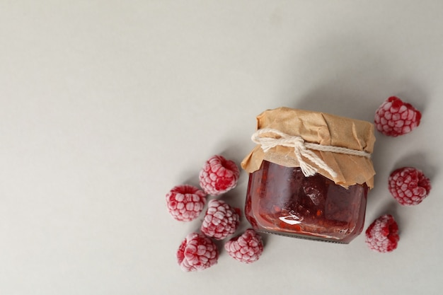 Jar of raspberry jam with ingredients on light gray background