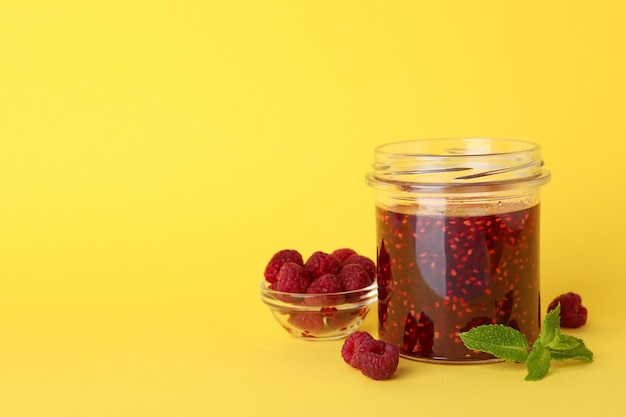 Jar of raspberry jam with ingredients on yellow background