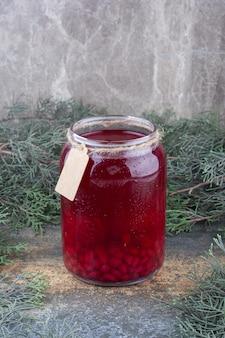 Un barattolo di succo rosso su fondo marmo. foto di alta qualità