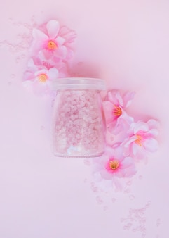 Jar of salt and artificial flowers on pink backdrop