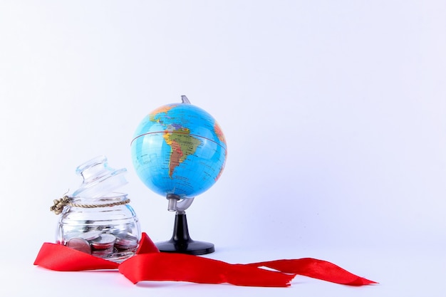 A jar of silver coins tied with a small string and a globe decorated with a red ribbon around it