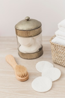 Jar of sponge; brush and towels in basket on wooden surface