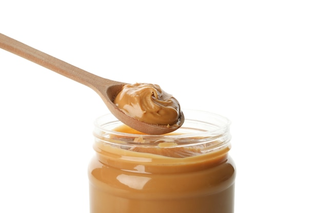 Jar and spoon with peanut butter isolated on white background