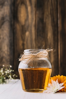 Jar of sweet honey and flowers on desk