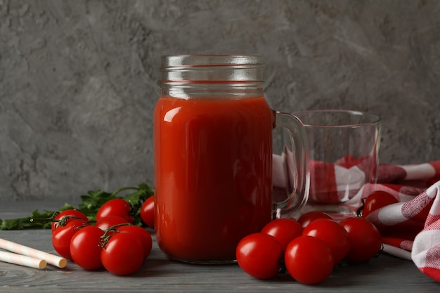 Jar of tomato juice, tomatoes and kitchen towel on wooden background