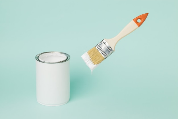 A jar of white paint and a levitating brush on a blue background. execution of painting works.