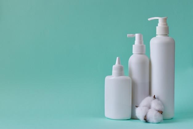 ベビーパウダー、タルカムパウダー、液体石鹸、シャワージェルのボトル、青い背景に分離された綿の瓶。ボディケア。スパリラックスベビー衛生。