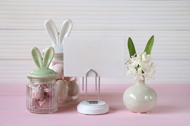バニーの耳イースターエッグ、ホワイトボード、白い木製の壁にピンクのテーブルにヒヤシンスの花が付いている瓶