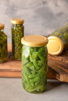 Jar with canned green beans on grey background