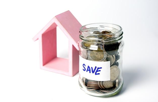 동전이 든 항아리와 집 부동산 투자로 라벨을 저장하고 미래의 돈 investm을 위해 돈을 절약합니다.