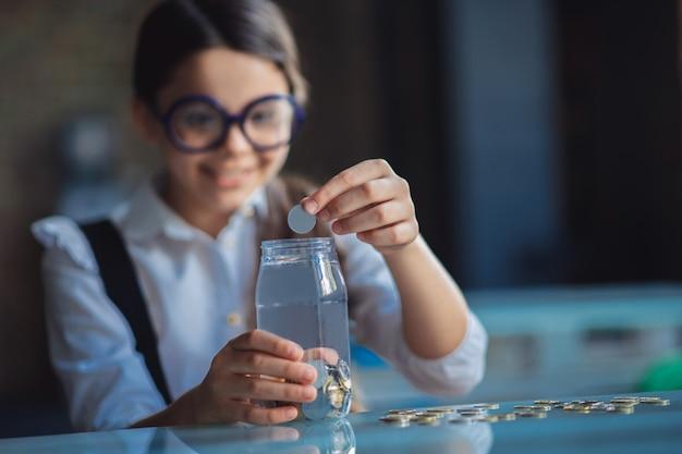Баночка с монетами. темноволосая девушка кладет монеты в банку и улыбается
