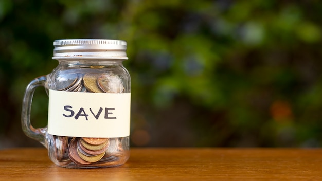 Jar with coins and save label outdoors