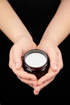 Баночка с косметическим увлажняющим кремом в женских руках