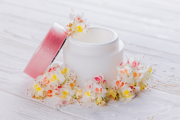 Jar with cream surrounded with flowers. organic cosmetics