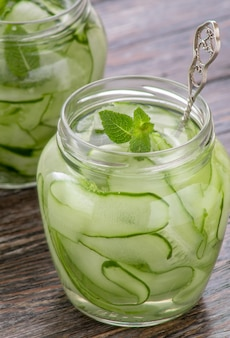 Jar with delicious cucumber lemonade on wooden table