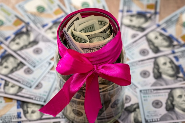 Jar with dollars with a pink ribbon