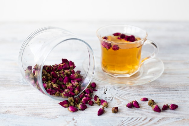Jar with dried flowers and cup of tea