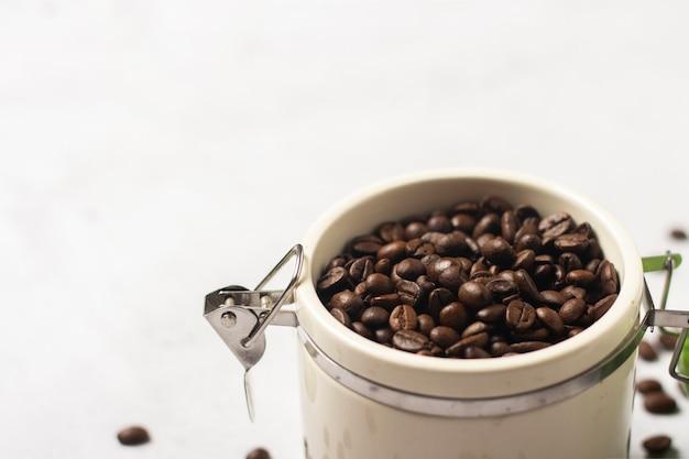 新鮮なコーヒー豆の入った瓶とコーヒー豆がコンクリートの空間に点在しています。バナー。新鮮なコーヒー、朝食、プランテーションのコンセプト
