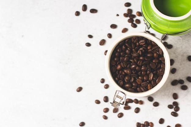 新鮮なコーヒー豆の入った瓶とコーヒー豆がコンクリートの空間に点在しています。バナー。新鮮なコーヒーのコンセプト