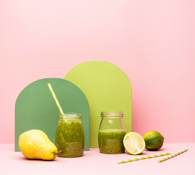 テーブルの上の梨とライムの新鮮なスムージーの瓶