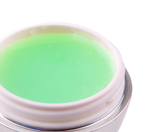 Jar with a green female face cream on white background