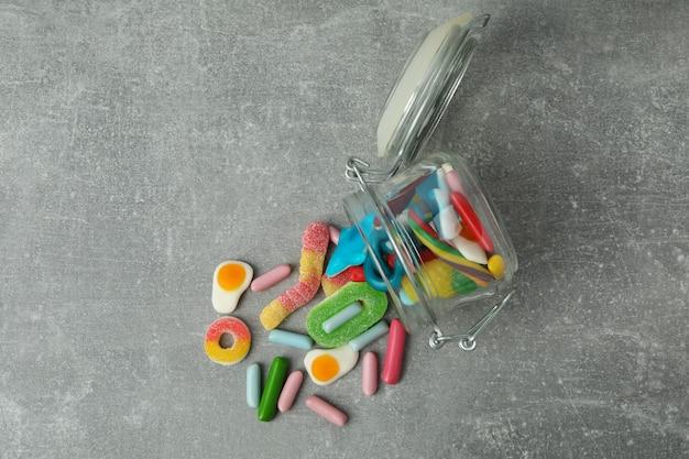 灰色のテクスチャ背景にグミキャンディーと瓶。