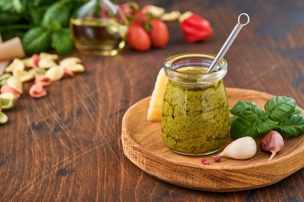 パルメザンチーズ、オリーブオイル、ソースペスト、バジル、ニンニクと素朴な背景に自家製ペストソースの瓶