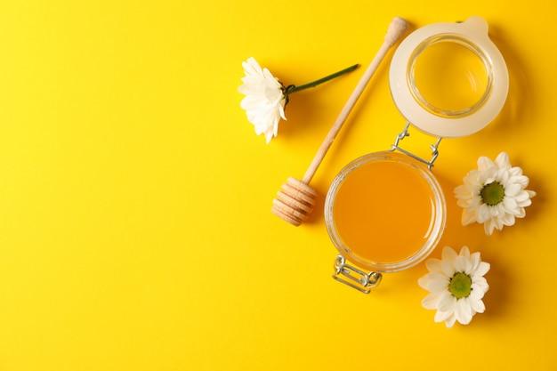 蜂蜜、ひしゃく、黄色の背景、テキスト用のスペースにカモミールの瓶