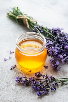 Jar with honey and fresh lavender flowers on a concrete background
