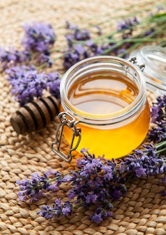 Jar with honey and fresh lavender flowers on a straw mat