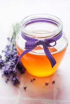 Jar with honey and fresh lavender flowers on a tile background