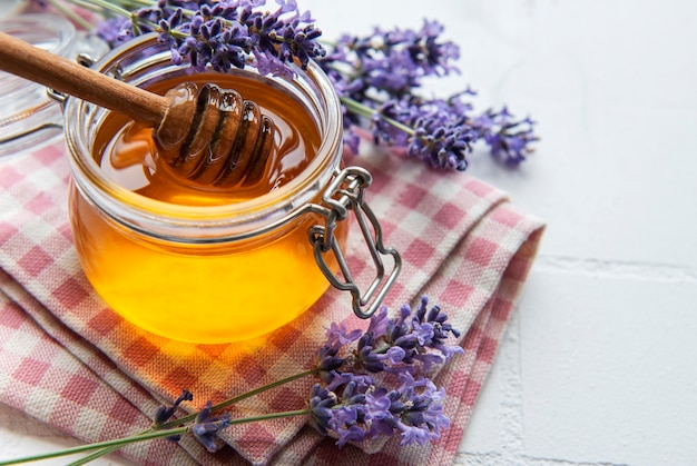 Jar with honey and fresh lavender flowers on a white tile background