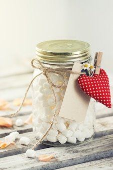 Jar with marshmallows and a heart hooked with a forceps