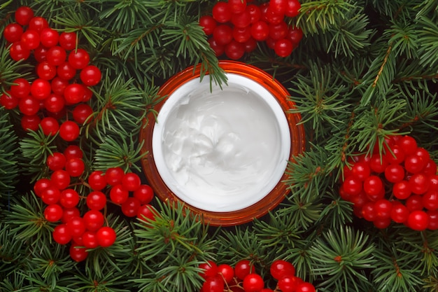 Jar with moisturizing face cream on the background of fir branches, conifers and berries of viburnum.