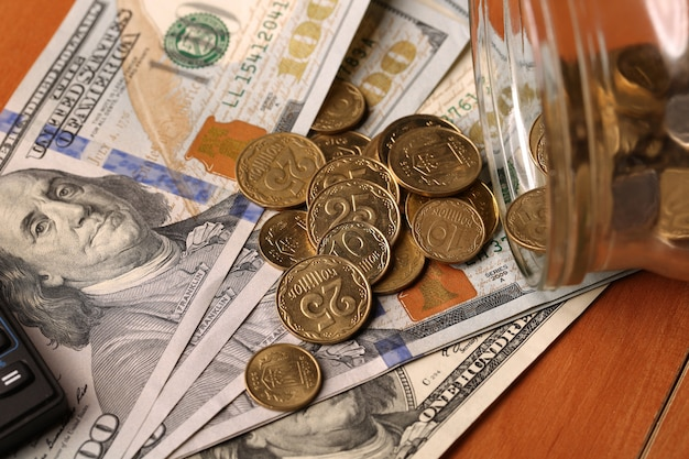 Jar with money falling coins for dollars, calculator on the background growth of blurred coins concept