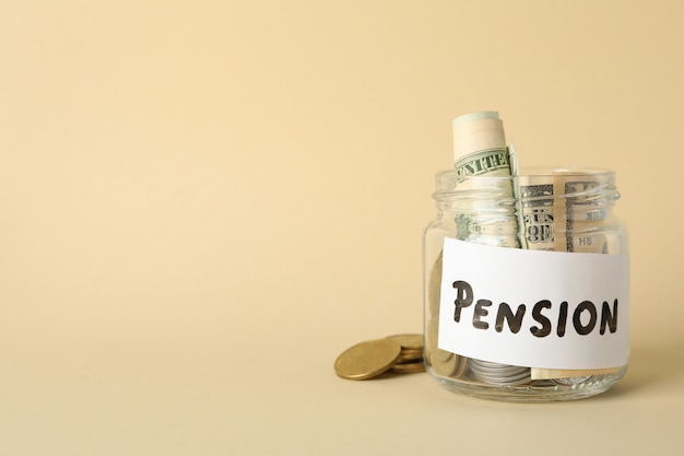 Jar with money and inscription pension on beige, space for text