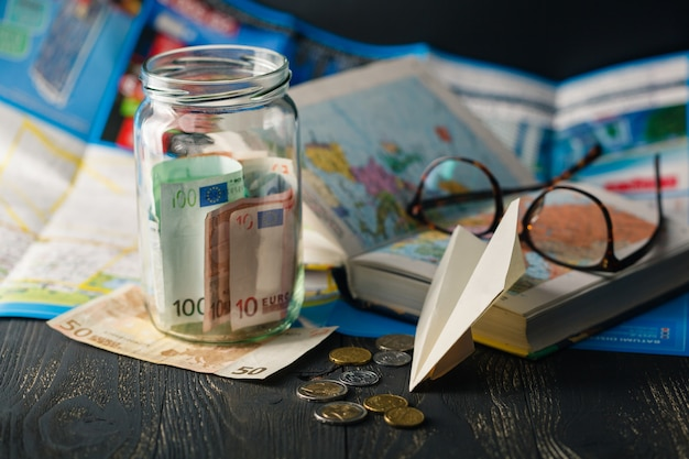 Jar with money for a travel, airplane, maps, passport, and other stuff for adventure