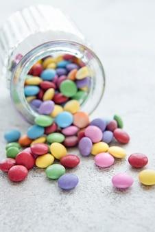 Банка с разноцветными конфетами драже на бетонном фоне