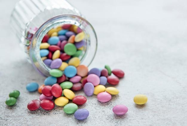 Банка с разноцветными конфетами драже на бетонном столе