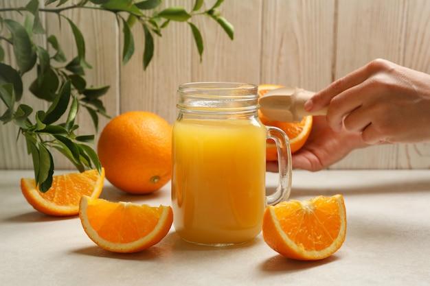 女性の手でジューサーとオレンジを保持している木製に対してオレンジジュースの瓶