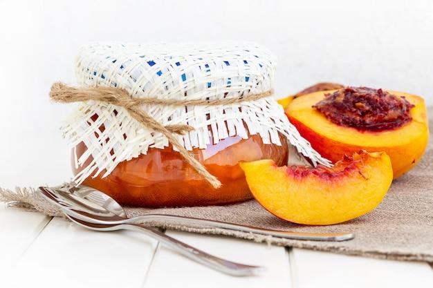 桃またはネクタリンジャム瓶入り。半分ネクタリンの果実。黄麻布ナプキン。白い木製の背景