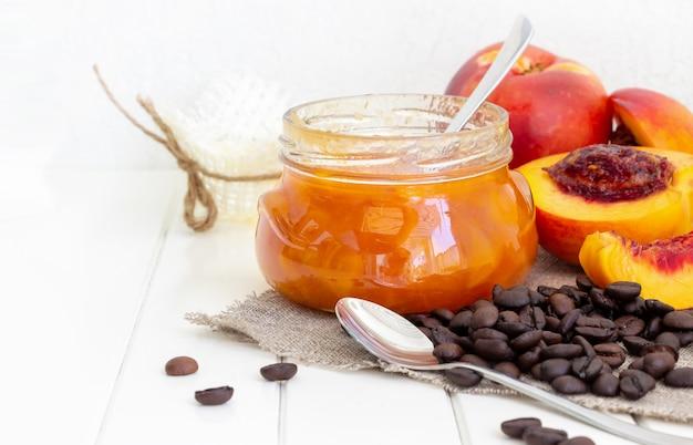 복숭아 또는 천도 복숭아 잼이있는 항아리. 반 천도 과일. 삼 베 냅킨에 커피 콩입니다. 흰색 나무 공간. 선택적 초점. 공간을 복사하십시오.