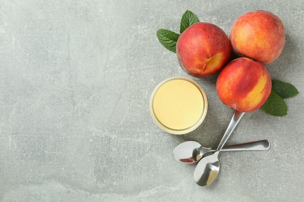 Jar with peach yogurt, peaches and spoons on gray background