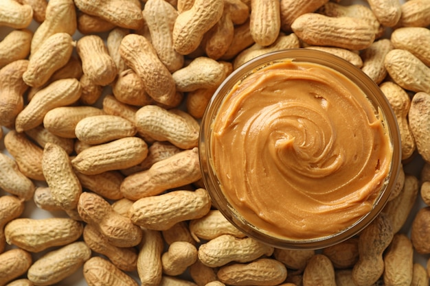 Jar with peanut butter on peanut background close up