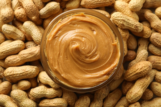 Jar with peanut butter on peanut background