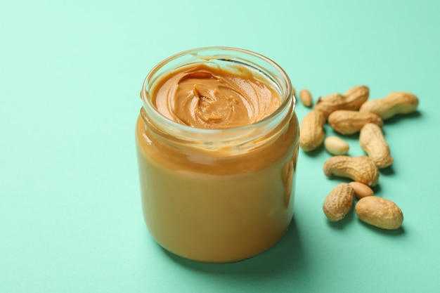 Jar with peanut butter and peanut on mint background
