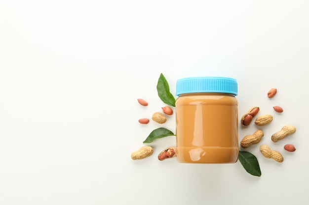 Jar with peanut butter, peanuts and leaves on white background