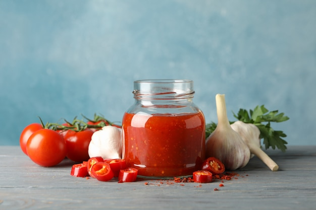 Jar with red chilli and tomato sauce, and spices on wooden table
